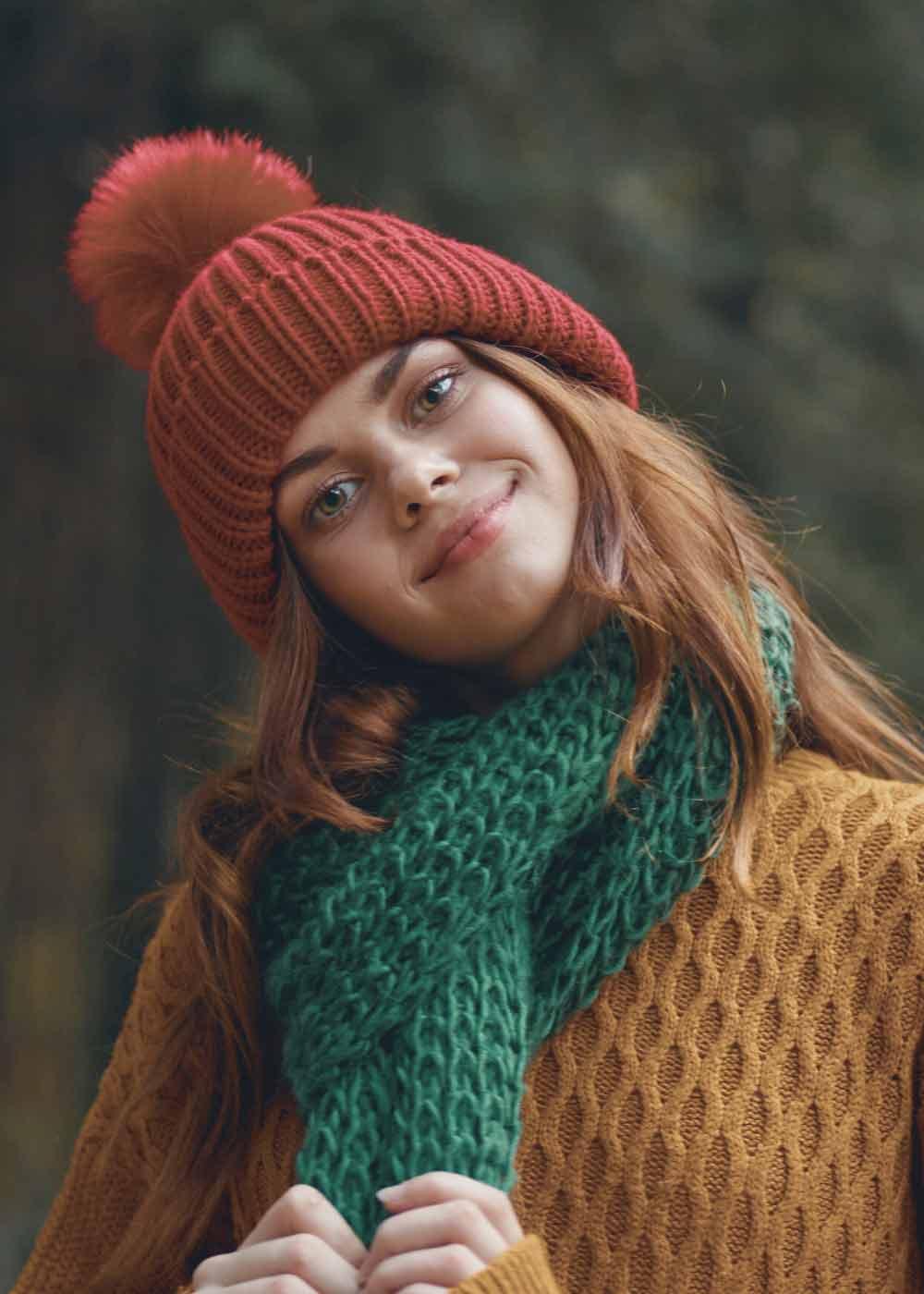 Frau mit Schal und Mütze traegt Accessoires